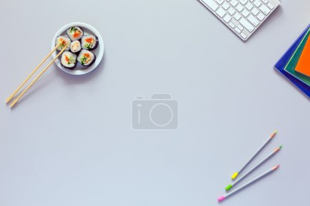 Top View of Office Work Place on grey Desk with Sushi