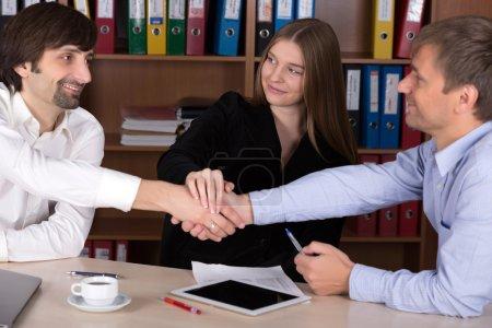 Photo pour Trois hommes d'affaires et dame serrant la main après avoir atteint un accord dans l'intérieur du bureau avec de nombreux dossiers de documents en couleur sur fond Focus sur le visage heureux de dame - image libre de droit