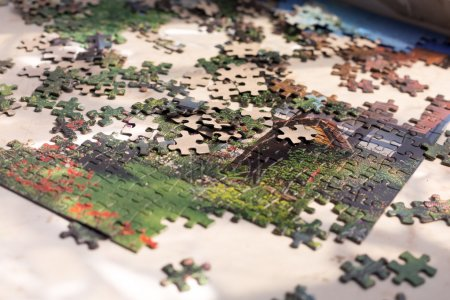Heap of colorful Puzzles elements on beige surface