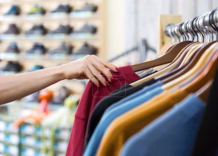 Row of Summer Seasonal Apparel and Hand of Customer in Shop