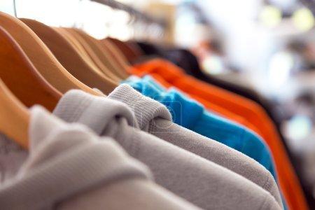 Photo pour Rangée de vêtements colorés Printemps saisonnier sur les épaules Cintres de gondole de magasin de détail avec d'autres articles sur fond - image libre de droit