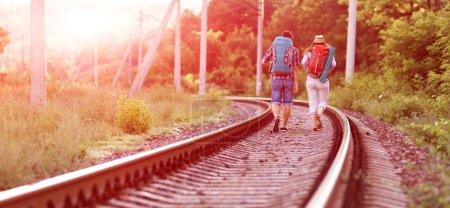 Photo pour Deux joyeux randonneurs homme et fille en vêtements de voyage décontractés avec sacs à dos marchant le long du chemin de fer avec contre-jour soleil et forêt sur fond - image libre de droit