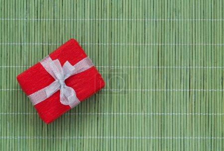 Geschenk mit verzierter Verpackung auf der grünen Bambusmatte