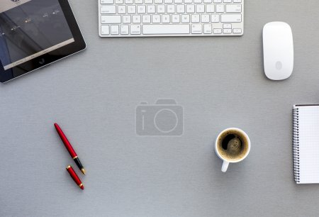 Photo for From above view on the well equipped working place surrounded with tablet PC, computer mouse and keyboard, red pen, blank notepad and cup of fresh coffee - Royalty Free Image