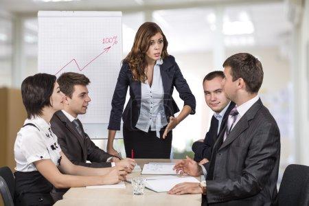 Photo pour La manager féminine parle énergiquement à son équipe. Quatre personnes sont assis autour de la table couverte s'agit de paperasse. Graphique de basculement et bureau ouvert d'espace sur l'arrière-plan - image libre de droit