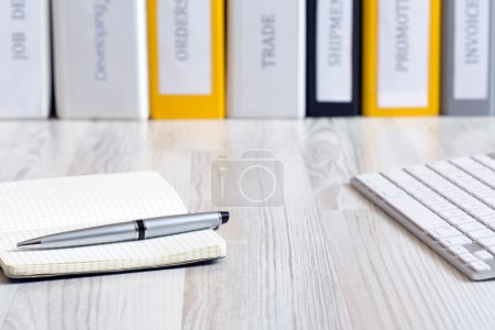 Photo for Side view on light wooded desk with pen, stylish leaver note pad and keyboard, with stack of folders on the background - Royalty Free Image