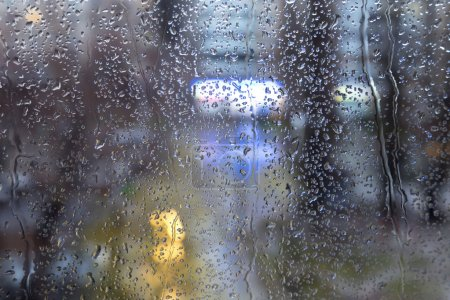 Raindrops on the window with evening city lights