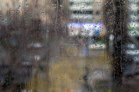 Photo pour Gouttes et ruisselle d'eau sur la surface du verre, flou fond urbain, néons colorés - image libre de droit