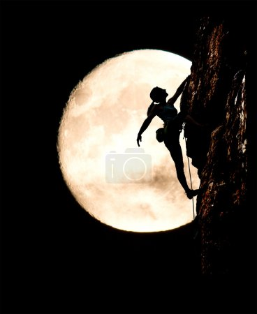 Female climber silhouette and large full moon background