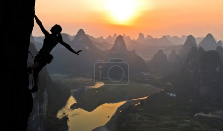 Photo for Elegant slim body of woman hanging on her hand on rock wall unusual China landscape with river karst mountains and sunset on background - Royalty Free Image