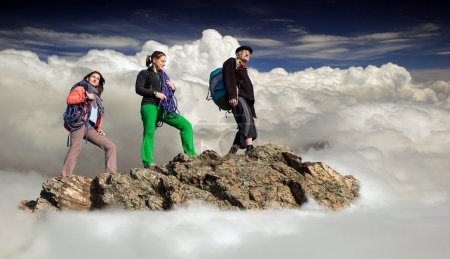 Group of climbers stays on the cliff surrounded with the sea of clouds