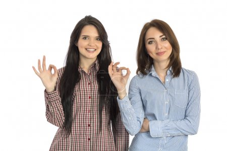 Two cheerful girls makes OK hand sign