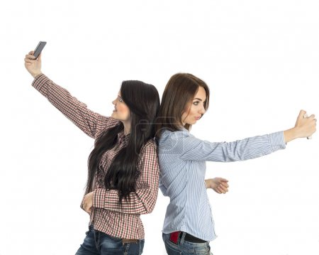 Photo for Two women stay backward and keep electronic gadgets in outstretched hands on white background - Royalty Free Image