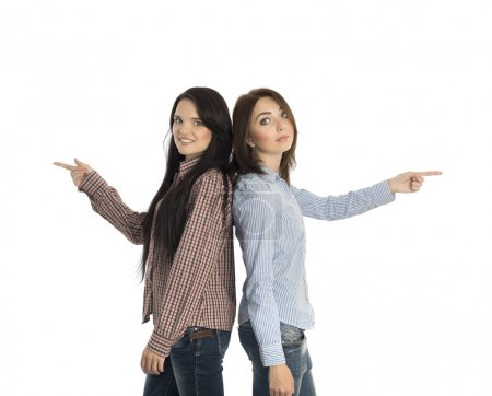 Two smiling girls pointing to opposite directions