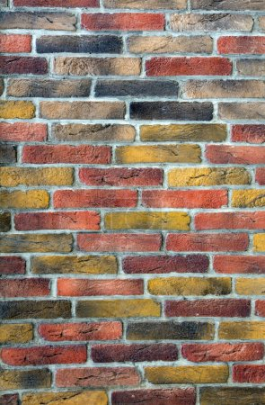 Photo for Image of brick wall made of many different colors individual bricks yellow red grey - Royalty Free Image
