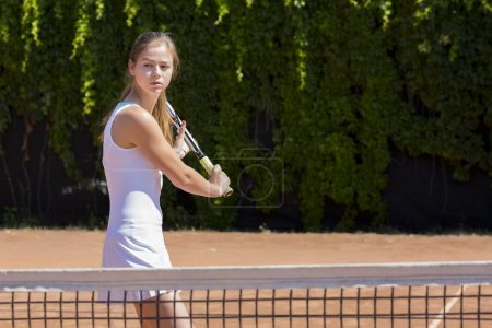 Young tennis athlete ready to return a ball