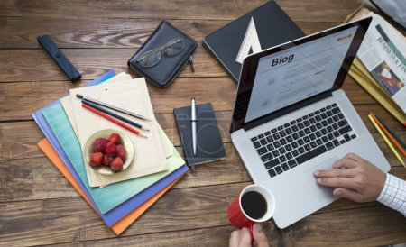 Photo for Concept man working on computer at unusual handcrafted rough wooden desk overhead top view keeping coffee mug with many office supplies in creative disorder focus on plate with fresh strawberry food - Royalty Free Image