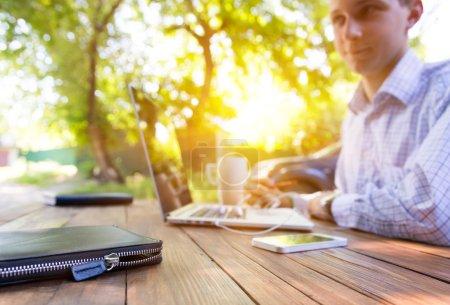 Photo pour Smart casual habillé personne travaillant sur ordinateur buvant tasse de café assis à un bureau en bois naturel rugueux en plein air avec arbre vert et soleil sur le fond - image libre de droit