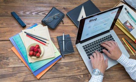 Photo pour Vue aérienne de l'homme tapant sur l'ordinateur portatif de clavier situé le bureau en bois normal de cru avec beaucoup d'articles dans le désordre désordonné créateur - image libre de droit