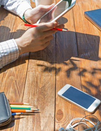 Wooden desk and man browsing gadget