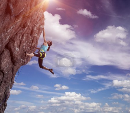 Elegant female athlete hanging at top of dangerous...