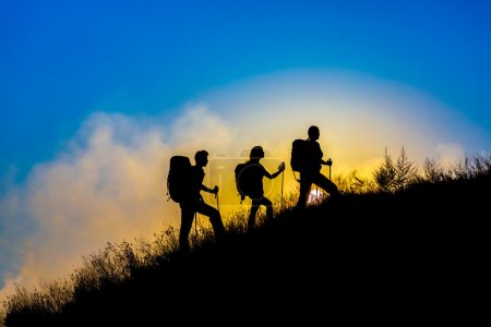Photo for Group of people silhouettes walking toward mountain summit with backpacks and hiking trekking gear meeting uprising sun sunbeams and blue sky of background - Royalty Free Image