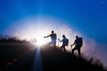 Photo pour Silhouettes de trois personnes marchant avec des sacs à dos et d'autres engins de randonnée vers le haut de l'herbe sauvage montagne mère père fille lumineux lever de soleil ciel arrière-plan - image libre de droit