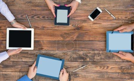 Photo pour Directement de la vue ci-dessus sur la main des personnes tenant des tablettes et des livres électroniques sous un bureau en bois bordé naturel - image libre de droit