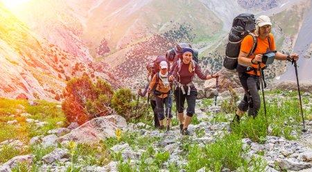 Photo pour Camping collectif gens approche haute altitude alpinisme avec lourds sacs à dos tonnes alpine gear marchant sur le sentier, chemin rocailleux à pics glaciers fond de ciel de neige soleil - image libre de droit