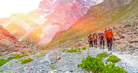 Photo pour Hommes et femmes montent avec sac à dos bagages et matériel de randonnée sur fond de paysage de montagne lumineux avec lever du soleil et hauts sommets derrière - image libre de droit