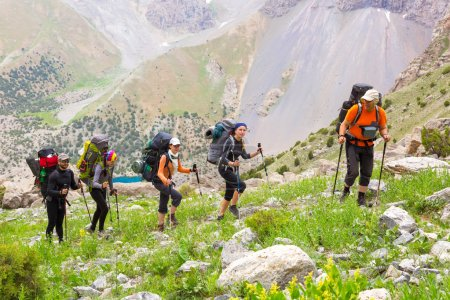 Photo for Mountain landscape and people walking with poles backpacks and other gear along dusty Asian trail with green grass and orange rocks around - Royalty Free Image