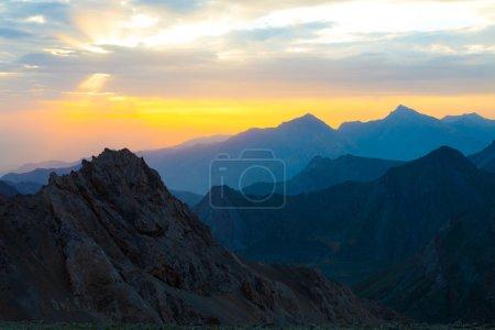Photo pour Silhouettes des crêtes de montagne et des crêtes des tons chauds et frais visibles de vue distance de soleil lumineux sur le fond - image libre de droit