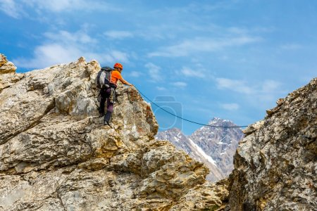 Photo for Male mountain climber moving on extreme sharp rock blue sky background climbing gear rope - Royalty Free Image