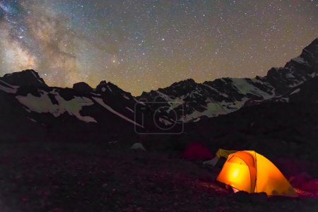 Photo for Silhouettes of snowy mountain peaks and edges night sky with many stars and milky way on background illuminated orange tent on foreground - Royalty Free Image