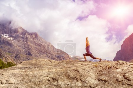 Photo for An attractive young woman doing a yoga pose for balance and stretching staying on top of high rock in the mountains with bright sun shining on background - Royalty Free Image