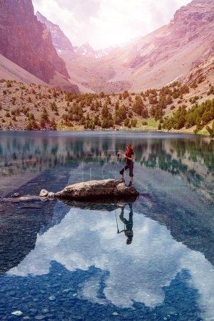 Photo pour Jeune tenue sportive style robe touriste féminin restant sur le rocher au milieu de sommets élevés lac de montagne azur et fond de soleil brillant - image libre de droit
