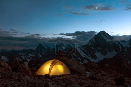 Photo pour Camping éclairé Tente jaune Nuit Croissant alpin de haute altitude dans le ciel bleu foncé ton plus chaud - image libre de droit