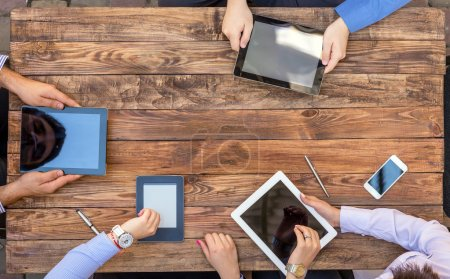 Photo for Natural Rough Wooden Plank Desk and Four People Holding Working Electronic Devices Tablet PC Looking on Hand Watches - Royalty Free Image