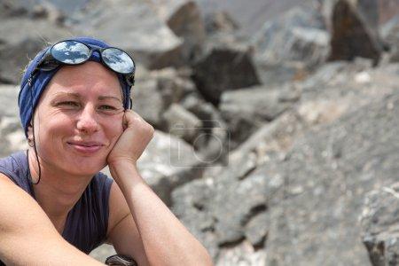 Photo pour Portrait de femme Climber Alpine joyeux et souriant avec tête bande et lunettes de soleil avec ciel reflet - image libre de droit