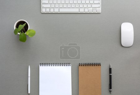 Photo for Classic Tone Wood Background Opened and Folded Beige Notepads Small Green Plant  Computer Mouse and Keyboard Top View - Royalty Free Image