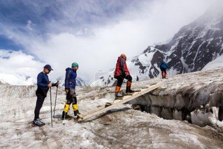 People Crossing Glacier Crevasse on Wood Shaky Footbridge