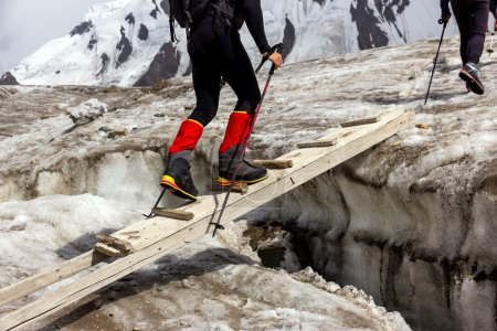 Photo for People Crossing Glacier Crevasse on Wood Shaky Footbridge Group of Mountain Climbers with High Altitude Boots and Clothing Crossing Ice Section During Ascent of Alpine Expedition in Asia Mountain Area - Royalty Free Image