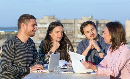 Photo pour Four People Casual Clothing Sitting Around Wooden Desk and Discussing Looking on Paper Work and Listening Arguments - image libre de droit
