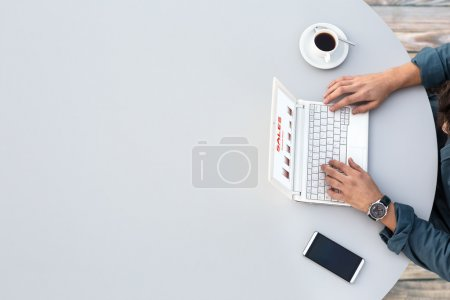 Photo for Grey Office Round Table and Man Working on Computer Top View Casual Clothing Typing on Keyboard with Marketing Chart on Screen Smart Phone and Cup of Coffee aside - Royalty Free Image