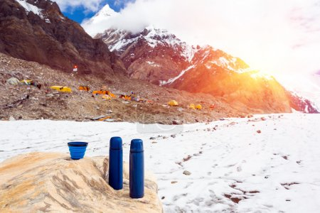 Two Blue travel thermoses Thermo Bottles and Cup on stone and Base Camp in High Mountains