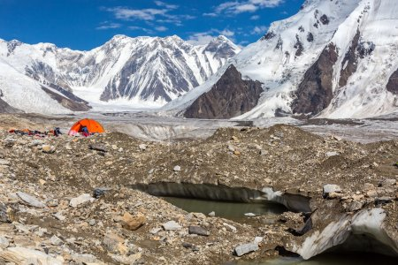Campsite on Glacier Moraine and Snowbound Mountain View with Sun Shining