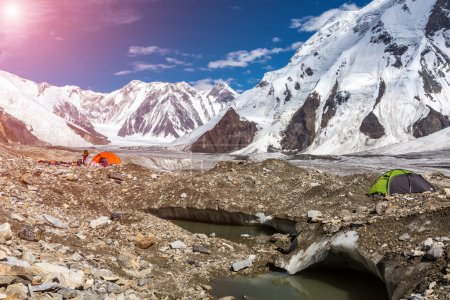 High Mountains Panorama with Red and Green Tents on Glacier Moraine and Shining Sun