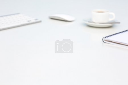 Soft Blurred Office Background with Computer Keyboard Mouse Coffee Mug and Notepad Side View Objects are Intentionally Blurred to Produce Low Contrast Background Image