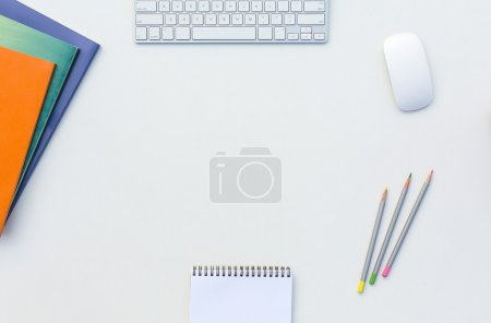 Photo for Image of White Office Desk with Computer Keyboard Mouse Color Pencils Booklets Glasses and other Supplies Top View - Royalty Free Image