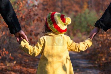 Photo pour Jeune famille marchant sur parc Alley Parents tenant mains de bébé fille des deux côtés automnal coloré forêt sur fond - image libre de droit